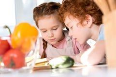 fokussierte Kinder, die Kochbuch beim zusammen kochen lesen stockbild