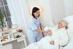Fokussierte Krankenschwester, die ruhige ältere Dame macht lizenzfreie stockfotografie