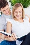 Fokussierte Paare, die zusammen ein Buch auf dem Sofa lesen lizenzfreie stockbilder