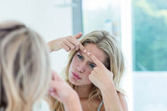 Fokussierte schöne junge Frau, die im Badezimmerspiegel betrachtet Lizenzfreie Stockfotos
