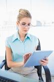 Fokussierte tragende Gläser der Geschäftsfrau unter Verwendung der Tablette Stockbild