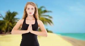 Fokussierte weiße Frau, die namaste mudra Geste vor Sommermeer tut stockbild