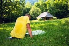 Fokussierter Abenteurer sitzt auf der grünen Bergwiese Lizenzfreie Stockfotos