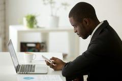 Fokussierter Afroamerikaner, der Telefon-E-Mail im Büro überprüft lizenzfreie stockbilder