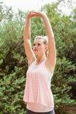 Fokussierter blonder Athlet, der Arme ausdehnt Lizenzfreie Stockfotos