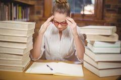 Fokussierter blonder Lehrer, der zwischen Büchern in der Bibliothek sitzt Lizenzfreie Stockfotos