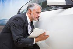 Fokussierter Geschäftsmann, der die Fahrzeugkarosserie betrachtet Lizenzfreie Stockfotografie