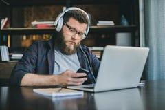 Fokussierter Geschäftsmann unter Verwendung des Smartphone beim Büro zu Hause bearbeiten Stockbild