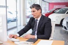 Fokussierter Geschäftsmann unter Verwendung seines Laptops Lizenzfreie Stockfotografie