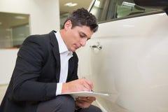 Fokussierter Geschäftsmann, der die Fahrzeugkarosserie betrachtet Stockfotos