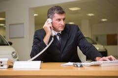 Fokussierter Geschäftsmann unter Verwendung des Laptops am Telefon Lizenzfreies Stockbild