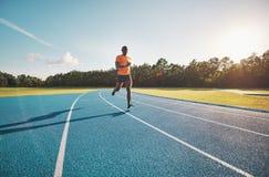 Fokussierter junger Athlet, der allein hinunter eine Bahn im Freien läuft stockbilder