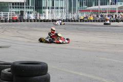Fokussierter kart Rennfahrer auf Stromkreis mit Reifenwand Lizenzfreies Stockbild