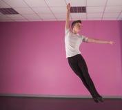 Fokussierter männlicher Balletttänzer, der oben springt Stockfotografie