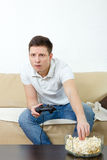 Fokussierter Mann, der das Videospiel hält Steuerknüppel und isst popco spielt lizenzfreie stockfotos