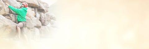 Fokussierter Mann, der ein großes Felsengesicht klettert stockfoto