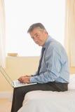 Fokussierter Mann, der einen Laptop sitzt auf einem Bett verwendet Stockbilder