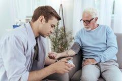 Fokussierter messender Blutdruck des Mannes lizenzfreies stockfoto