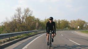 Fokussierter Radfahrer auf einem Straßenfahrradreiten in Richtung zur Kamera bei Sonnenuntergang Radfahrer, der schwarzes Trikot  stock video