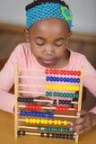 Fokussierter Schüler, der mit Abakus in einem Klassenzimmer berechnet Stockfoto