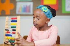 Fokussierter Schüler, der mit Abakus in einem Klassenzimmer berechnet Lizenzfreies Stockfoto