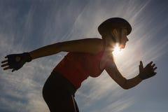 Fokussierter sportlicher blonder Eislauf gegen blauen Himmel Stockfotos