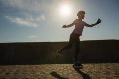 Fokussierter sportlicher blonder Eislauf gegen blauen Himmel Lizenzfreies Stockfoto