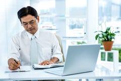 Fokussiertes asiatisches Geschäftsmannschreiben Lizenzfreies Stockfoto