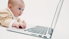 Fokussiertes Baby, das am Laptopschirm aufpasst Stockfotografie