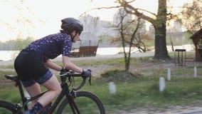 Fokussiertes geeignetes weibliches Radfahrerreiten aus dem Sattel heraus Folgen Sie Seitenansicht des M?dchentrainings auf einem  stock video