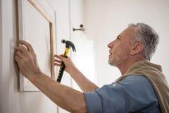 Fokussiertes hängendes Bild des älteren Mannes auf Wand am neuen Haus Stockfoto