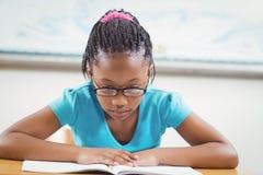 Fokussiertes Schülerlesebuch in einem Klassenzimmer Lizenzfreie Stockfotos