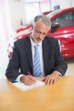 Fokussiertes Verkäuferschreiben auf Klemmbrett an seinem Schreibtisch Stockfotografie