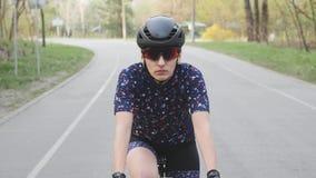 Fokussiertes weibliches Radfahrerreitfahrrad im Park Front View Tragender schwarzer Sturzhelm und Gl?ser Langsame Bewegung