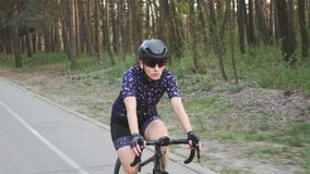 Fokussiertes weibliches Reitenfahrrad des Proradfahrers im Park Getrennt auf Wei? radfahren Langsame Bewegung