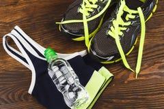 Folâtre des articles : espadrilles, bouteille de l'eau et soutien-gorge de sports Photographie stock libre de droits