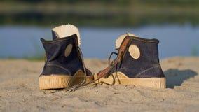Folâtre des chaussures de gymnase sur un sable Photo libre de droits