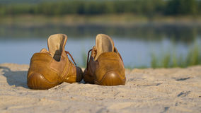 Folâtre des chaussures de gymnase sur un sable Photographie stock libre de droits