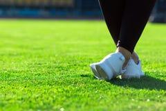 Folâtre des jambes de jeune femme sportive dans les collants foncés et le sne léger Photos stock