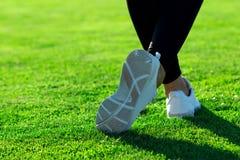Folâtre des jambes de jeune femme sportive dans les collants foncés et le sne léger Images stock