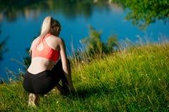 Folâtre la blonde de fille dans un T-shirt rouge assis pour attacher des dentelles sur des espadrilles en parc près de la rivière Photos stock