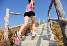 Folâtre la femme courant aux escaliers de montagne Photographie stock