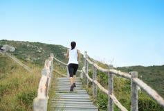 Folâtre la femme courant sur des escaliers de montagne Photographie stock
