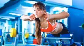 Folâtre la jeune femme faisant des exercices sur la machine de dos d'entraîneur dans le gymnase Image libre de droits