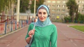 Folâtre la jeune fille musulmane avec un sac à dos sur la voie sportive banque de vidéos