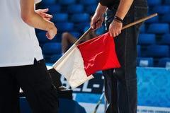 Folâtre le fonctionnaire avec des drapeaux dans la main Image libre de droits