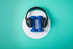 Folâtrez à plat la composition en configuration avec des haltères et des écouteurs photos stock