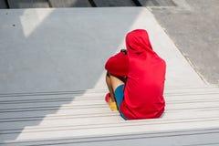 Folâtrez l'homme dans le capot rouge se reposant sur des escaliers et regardez sa montre, s Image libre de droits