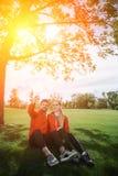 Folâtrez l'homme et la femme faisant des selfies en parc Photo stock