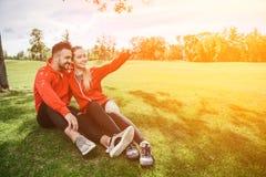 Folâtrez l'homme et la femme faisant des selfies en parc Image libre de droits